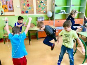 czworo uczniów próbuje skakać przez nitkę, włóczkę