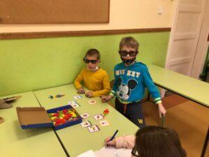 dwóch uczniów w specjalnych okularach utrudniających widoczność próbuje ułożyć odpowiedni obrazek z mozaiki