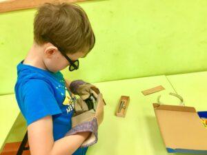 chłopiec w roboczych rękawicach i w zamazanych okularach próbuje nakręcić śrubę na gwint