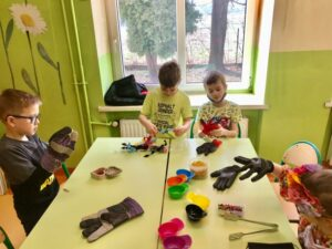 uczniowie w rękawicach roboczych nawlekają makaron na drucik kreatywny, sortują pomponiki do odpowiednich pojemników, rozplątują spinacze.