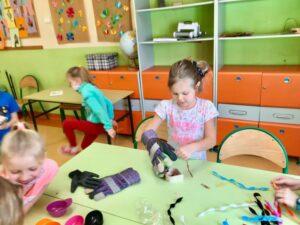 dziewczynka w dużych rękawicach rozplątuje spinacze, w oddali skacząca przez włóczkę inna uczennica