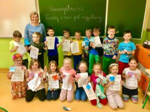 """grupa uczniów trzymających kolorowanki z napisem lubię siebie z nauczycielką, w tle tablica z napisem """"Każdy z nas jest wyjątkowy"""