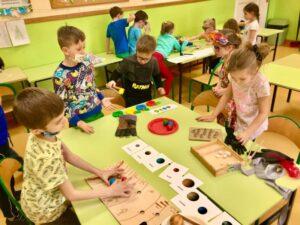 dzieci wkładają drewnianymi szczypcami - planety w odpowiednie miejsca, kuleczki do odpowiedniego koloru jabłka, białe kamyki do kartonowych podstawek