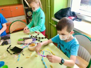 dziewczynka i chłopiec nawlekają makaron na kolorowe druciki kreatywne